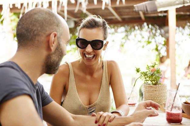 Glückliche frau, die sonnenbrille und spitze mit niedrigem hals trägt, sitzt im straßencafé mit gutaussehendem mann, berührt seinen arm und lacht. nettes paar, das zeit zusammen während der ferien verbringt.