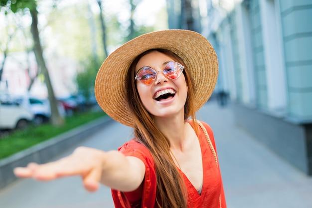 Glückliche frau, die spaß hat und sommer im trendigen hut mit schwarzem band genießt, der sonnenschein genießt.