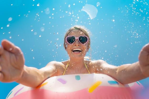 Glückliche frau, die spaß im sommerurlaub im freien gegen blauen himmel hat