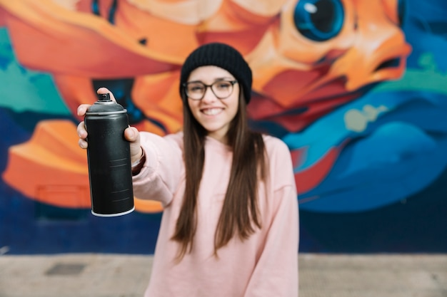 Glückliche frau, die sprühflasche in der front vor graffitiwand hält