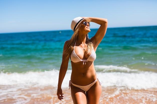 Glückliche frau, die strand genießt, der im sommer durch tropisches blaues wasser freudig entspannt