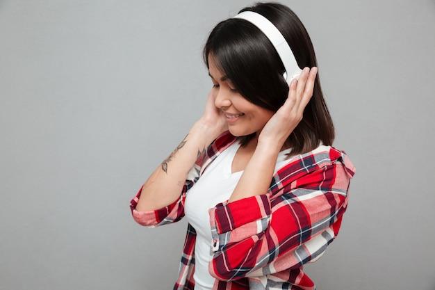 Glückliche frau, die über graue wand steht, die musik mit kopfhörern hört.