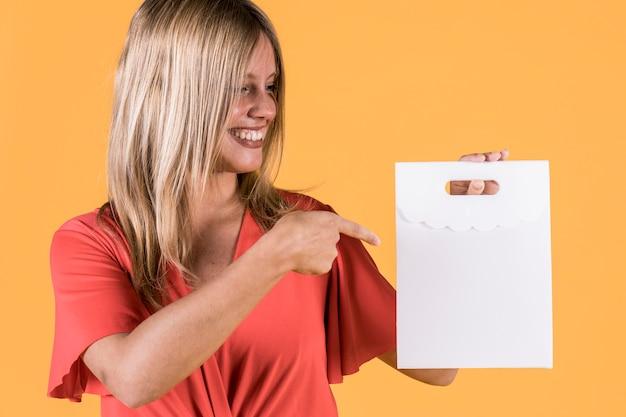 Glückliche frau, die über weiße papiertüte auf farbigem hintergrund zeigt