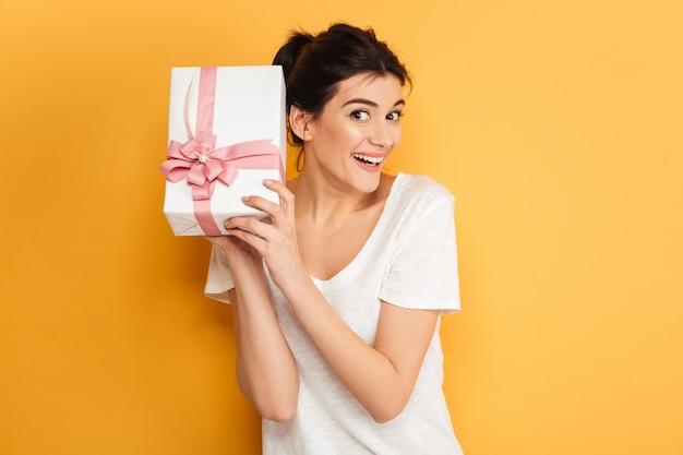 Glückliche frau, die überraschungsgeschenkboxgeschenk hält