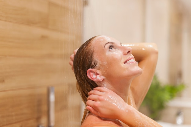 Glückliche frau, die unter der dusche entspannt