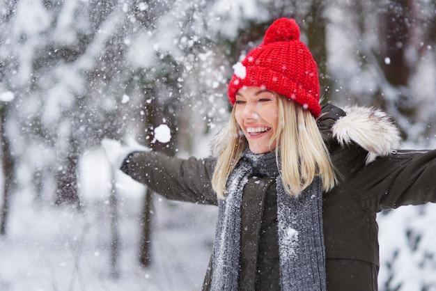 Glückliche frau, die unter schneeflocke tanzt