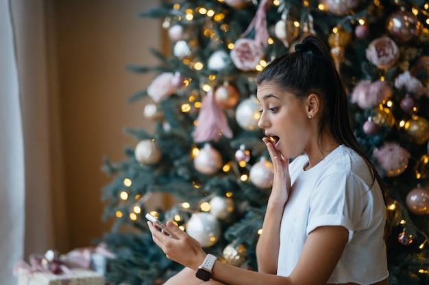 Glückliche frau, die videoanruf mit ihrer familie oder freunden hat. junge frau verwendet eine digitale tafel nahe geschmücktem festlichem baum zu hause.