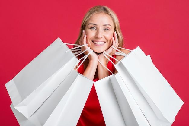Glückliche frau, die viele einkaufstaschen nach dem einkaufsbummel hält