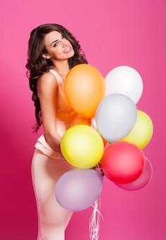 Glückliche frau, die viele luftballons hält