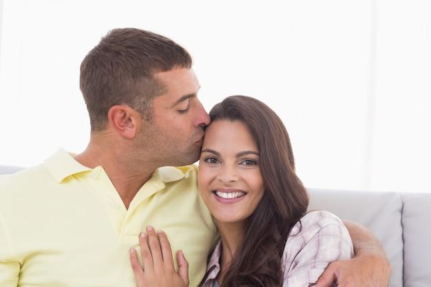 Glückliche frau, die vom mann geküsst wird