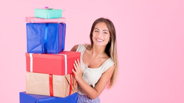 Glückliche frau, die vom stapel der bunten geschenkboxen gegen rosa hintergrund späht