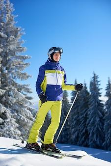 Glückliche frau, die vor dem skifahren auf skiern posiert. sonniger tag im skigebiet. klarer blauer himmel, schneebedeckte tannen im hintergrund.