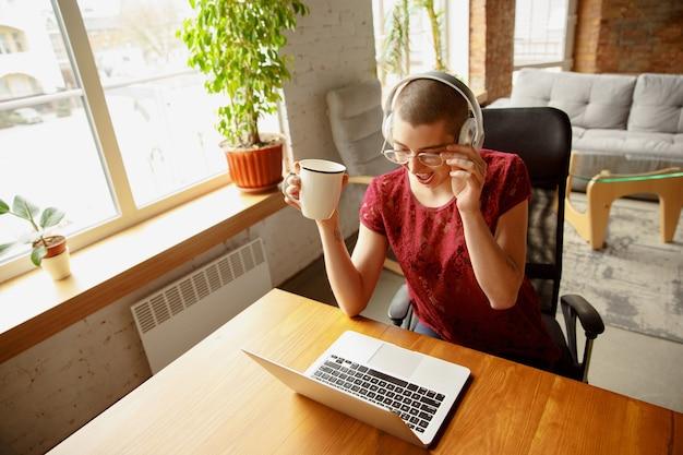Glückliche frau, die während der quarantäne von coronavirus oder covid-19 von zu hause aus arbeitet, remote-office-konzept. schönes kahles modell, manager, der aufgaben mit laptop, telefon erledigt, hat online-konferenz, treffen.