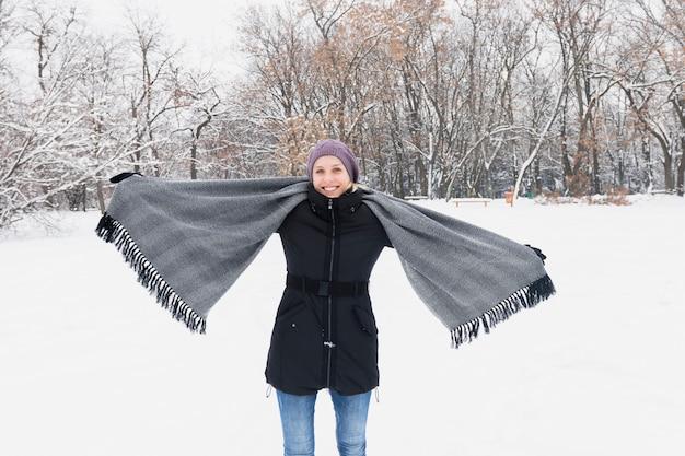 Glückliche frau, die warme kleidung trägt und den gemütlichen schal steht auf schneebedecktem land im winter hält