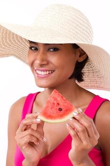 Glückliche frau, die wassermelone hält, zu ihnen schaut und lächelt