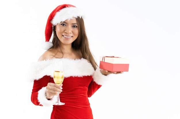 Glückliche frau, die weihnachtsgeschenkbox und -becher mit champagner hält