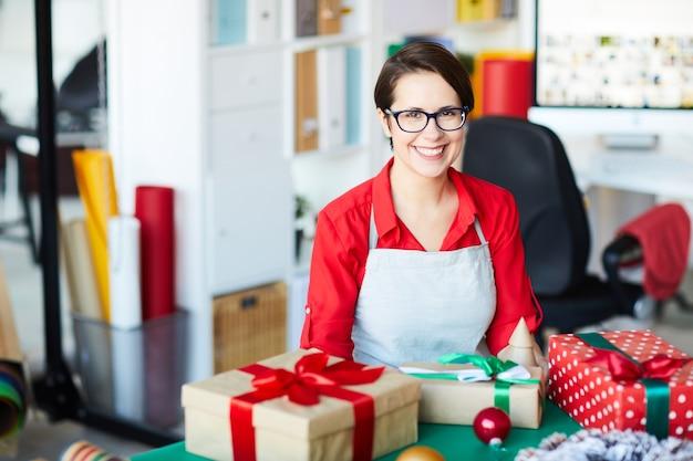 Glückliche frau, die weihnachtsgeschenke oder -geschenke verpackt
