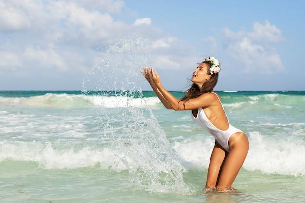 Glückliche frau, die weißen bikini trägt, spielt und plätschert im meer