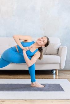Glückliche frau, die yoga zu hause auf der matte tut