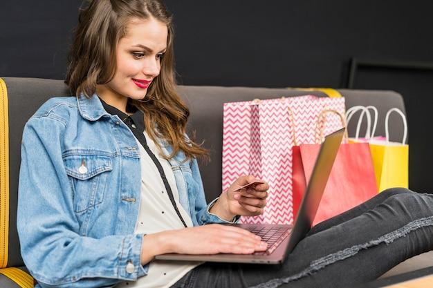 Glückliche frau, die zu hause das onlineeinkaufen genießend sitzt