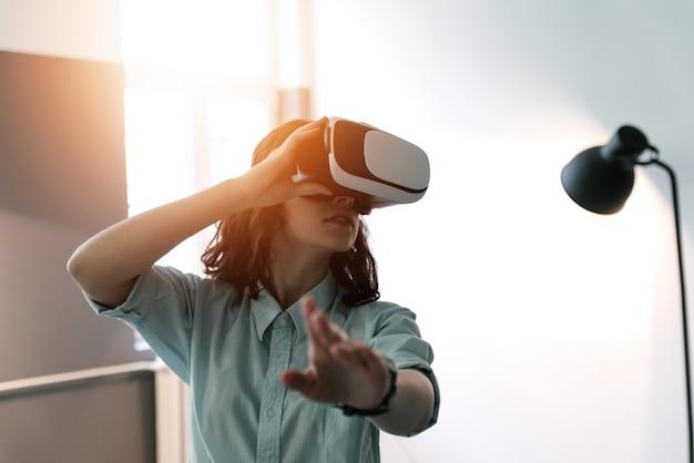 Glückliche frau, die zu hause erfahrung unter verwendung der vr-kopfhörergläser der virtuellen realität erhält