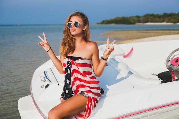 Glückliche frau eingewickelt in amerikanische flagge auf tropischen sommerferien, die auf boot im meer reisen, party am strand, leute, die spaß zusammen haben, positive emotionen