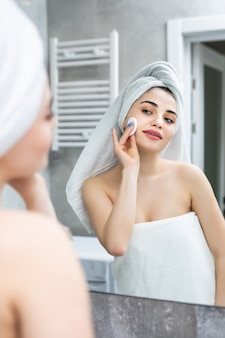 Glückliche frau entfernt make-up reinigungspads lotion badezimmerspiegel im badezimmer