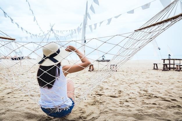 Glückliche frau entspannen in der hängematte am strand