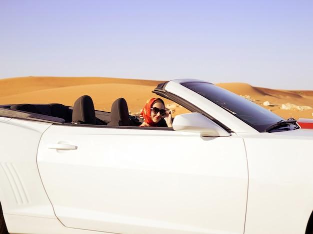 Glückliche frau fährt auf der wüstenstraße am cabrio