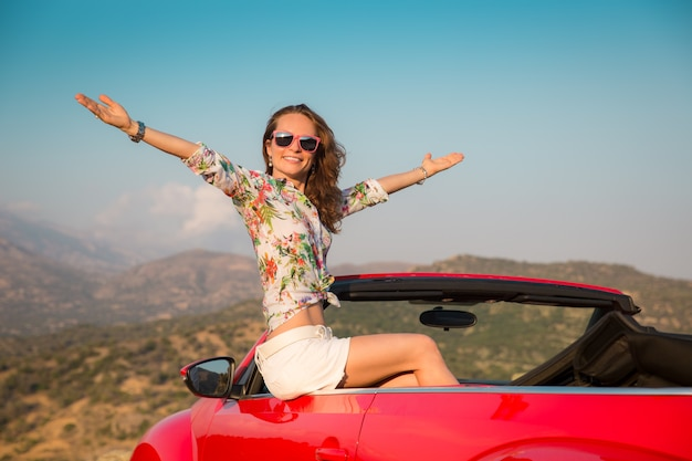 Glückliche frau fährt mit dem auto in den bergen mädchen, das spaß im roten cabriolet sommerferienkonzept hat