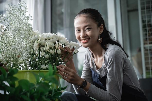 Glückliche frau floristin tragen schürze, die nach einem schönen blumenstrauß riecht