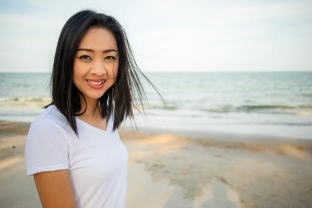Glückliche frau gehen auf dem strand spazieren.