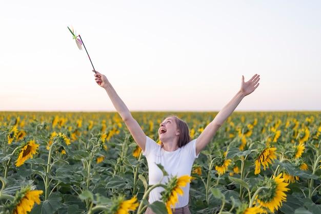 Glückliche frau geht durch sonnenblumenfeld. hände erhoben.