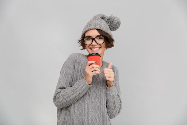 Glückliche frau gekleidet im pullover und im warmen hut, der kaffee trinkt.