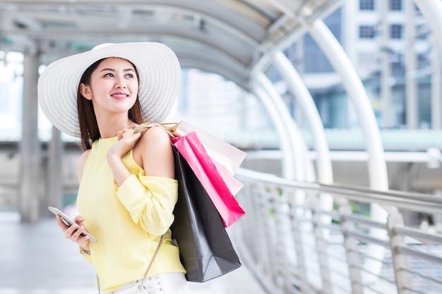 Glückliche frau genießen einkaufstasche, handy in der stadt mit sommerschlussverkauf im shop