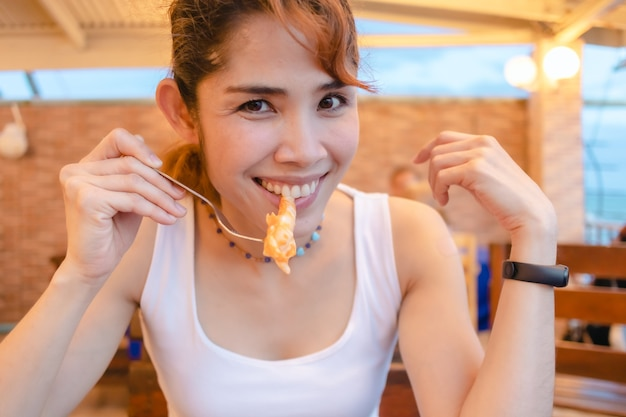 Glückliche frau genießt es, in den sommerferien tintenfischmeeresfrüchte zu essen