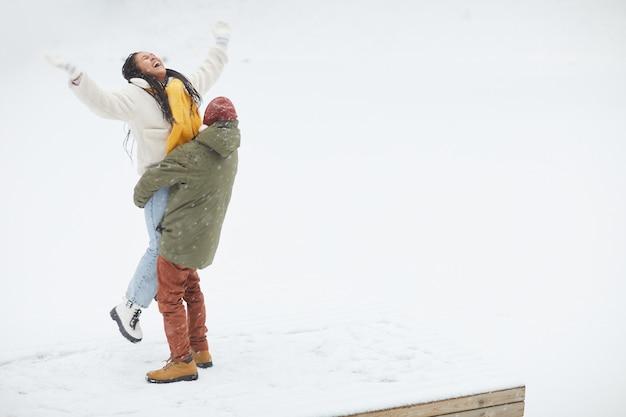 Glückliche frau glücklich mit winter und schnee zusammen mit mann, der sie in seinen händen hält