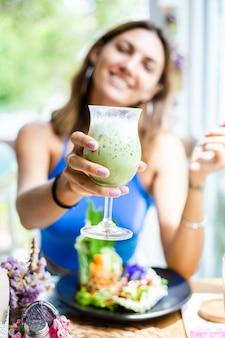 Glückliche frau hält japanischen matcha-grüntee mit eis im glas im café frau mit gesundem antioxidansgetränk im sommer süßes café