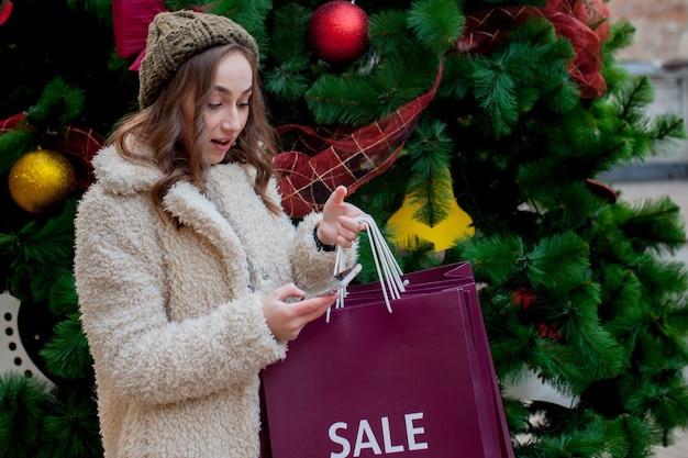 Glückliche frau hält papiertüten mit symbol des verkaufs in den geschäften mit verkäufen zu weihnachten,