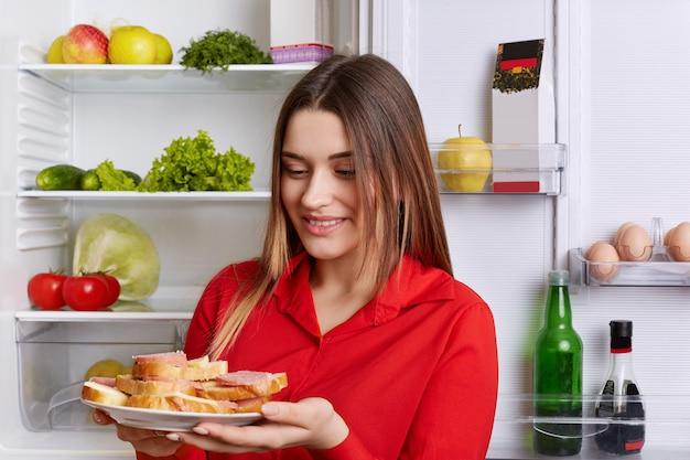 Glückliche frau hält teller mit fertigen sandwiches, trägt rote bluse, wird snack essen, steht vor geöffnetem kühlschrank voller produkte. schöne fröhliche frau mit leckeren sandwiches in der küche