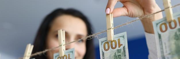 Glückliche frau hängt saubere dollars an wäscheklammern, um das konzept der schmutzigen geldwäsche zu trocknen