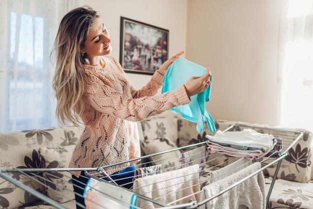 Glückliche frau hausfrau hängen saubere kleidung am trockner nach dem waschen zu hause