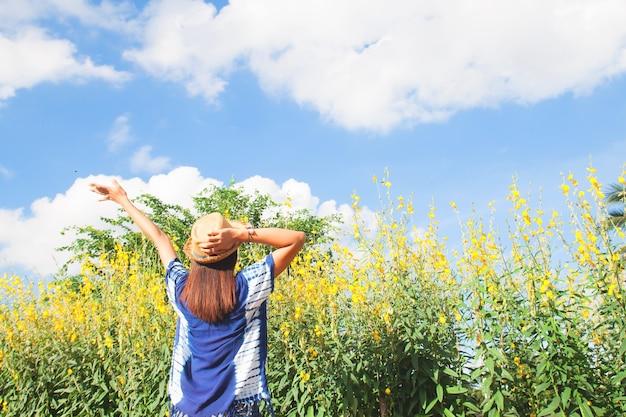 Glückliche frau heben hand in gelbe blume feld mit blauem himmel