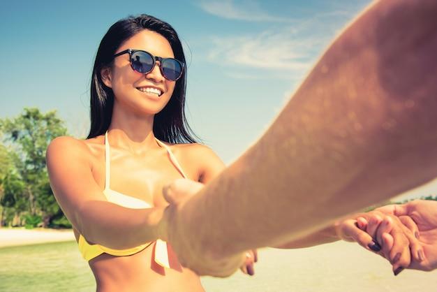 Glückliche frau im badeanzug, die hände ihres freundes zieht und sommerferienzeit am strand genießt