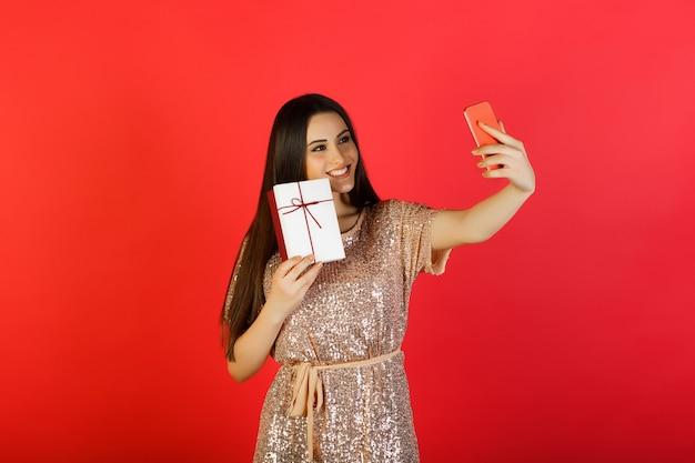 Glückliche frau im beige kleid, das selfie mit telefon nimmt und geschenkbox in der hand hält