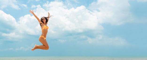 Glückliche frau im bikini, der am strand im sommer springt
