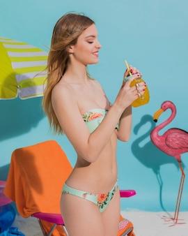 Glückliche frau im bikini, der cocktail hält