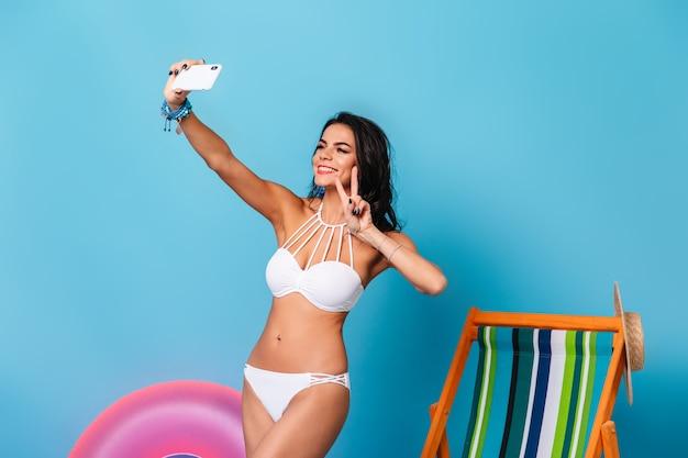 Glückliche frau im bikini, die selfie nimmt