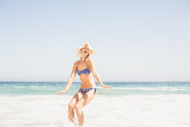 Glückliche frau im bikini und in hut, die spaß auf dem strand haben