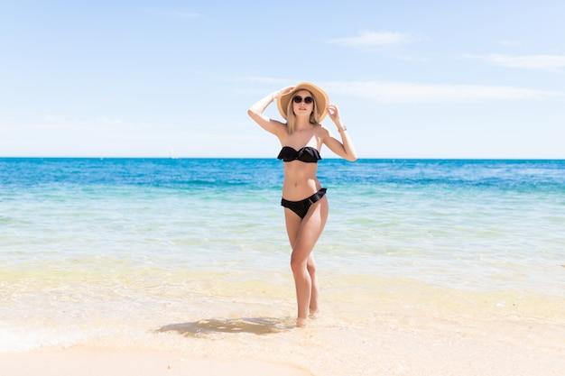 Glückliche frau im bikini und sonnenhut in der sonnenbrille am meeresstrand